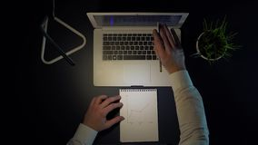 A man sits at a table and draws a graph of income in a notebook while sitting at a laptop in the evening.4k. A man in a white shirt sits at a table and draws a stock video
