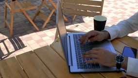 A man in a white shirt sits at a table in a street cafe, typing on a laptop keyboard. view from above. 4k. 4k video.  stock video