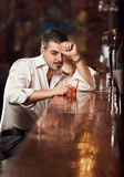 man in white shirt sitting near bar desk with whiskey Stock Images