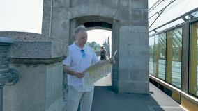 A man in a white shirt stands on a bridge and looks at a paper map of the city. A middle-aged man in a white shirt and light trousers, stands on an old bridge stock video