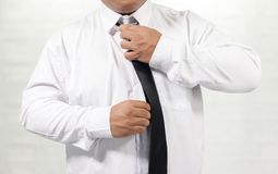 Man in white shirt taking off neck tie Royalty Free Stock Image