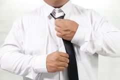 Man in white shirt taking off neck tie Royalty Free Stock Photos