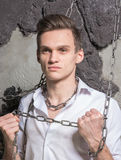 A man in a white shirt and tie breaks the chain. Royalty Free Stock Photography