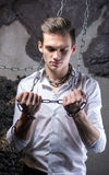 A man in a white shirt and tie breaks the chain. Stock Photo