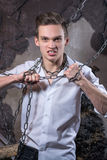A man in a white shirt and tie breaks the chain. Royalty Free Stock Image