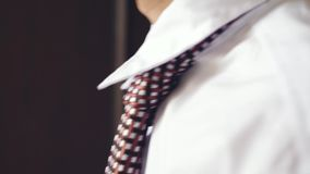 Man in white shirt tying a tie in the profile view. 3840x2160 stock video