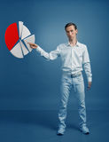 Man in white shirt working with pie chart on blue background. Young man in white shirt working with pie chart on blue background. Concept on the topic of Royalty Free Stock Photography