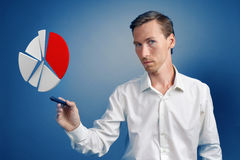 Man in white shirt working with pie chart on blue background. Young man in white shirt working with pie chart on blue background. Concept on the topic of Royalty Free Stock Photo