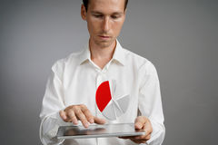 Man in white shirt working with pie chart on a tablet computer, application for budget planning or financial statistics. Young man in white shirt working with a royalty free stock photos