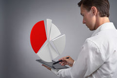 Man in white shirt working with pie chart on a tablet computer, application for budget planning or financial statistics. Royalty Free Stock Photos