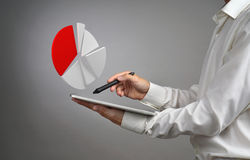Man in white shirt working with pie chart on a tablet computer, application for budget planning or financial statistics. Royalty Free Stock Images