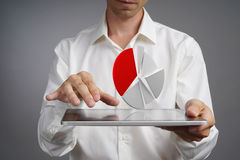 Man in white shirt working with pie chart on a tablet computer, application for budget planning or financial statistics. Royalty Free Stock Photo