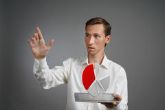 Man in white shirt working with pie chart on a tablet computer, application for budget planning or financial statistics. Young man in white shirt working with a stock image