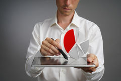 Man in white shirt working with pie chart on a tablet computer, application for budget planning or financial statistics. Young man in white shirt working with a royalty free stock photography
