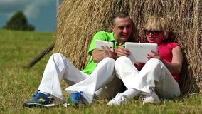 Man with white smartphone and woman with white tablet PC sits near a haystack stock footage