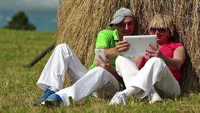 Man with white smartphone and woman with white Tablet-PC sits near haystack stock footage