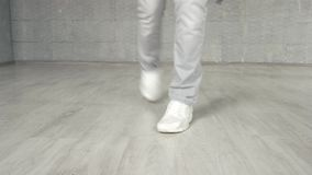 Man in white sneakers performing dance moves. Legs of modern style dancer in dance position. Studio of contemporary dance stock video footage