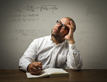 Man in white is solving equation Stock Images