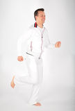 Man in white sports suit runs barefoot Stock Photos