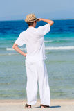 Man in a white suit against the sea stock image
