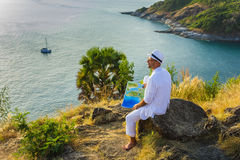 The man  in a white suit and hat sitting on a rock on the sea ba Stock Image