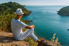 The man  in a white suit and hat sitting on a rock on the sea ba Royalty Free Stock Photo