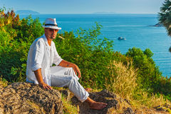 The man  in a white suit and hat sitting on a rock on the sea ba Royalty Free Stock Photography