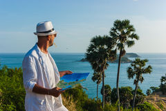 The man in a white suit and hat sitting on a rock on the sea ba Royalty Free Stock Images