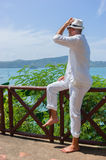 man in a white suit sits on the waterfront Royalty Free Stock Image