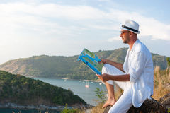 Man in a white suit sitting on the beach with a map Royalty Free Stock Images