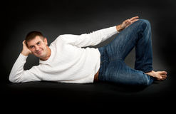 Man in a white sweater lying Royalty Free Stock Photo