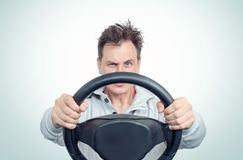 Man in a white sweatshirt with steering wheel, on background. Car driver concept royalty free stock image