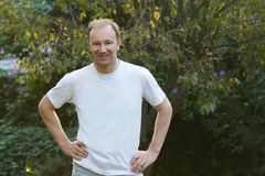 Man in White T Shirt. Man, white, tshirt, standing, outdoors, male, top, torso, hips, smile, people, masculine, pose, Caucasian, Anglo-saxon, garden stock photo