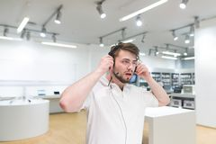Man in a white T-shirt and a beard selects headphones in the electronics store. Buying headphones. Portrait of a buyer who listens to music in headphones on the stock image