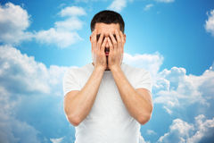 Man in white t-shirt covering his face with hands. People, crisis, emotions and stress concept - man in white t-shirt covering his face with hands over blue sky Royalty Free Stock Images
