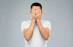 Man in white t-shirt covering his face with hands. People, crisis, emotions and stress concept - man in white t-shirt covering his face with hands over gray Royalty Free Stock Image
