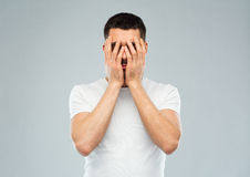 Man in white t-shirt covering his face with hands. People, crisis, emotions and stress concept - man in white t-shirt covering his face with hands over gray Royalty Free Stock Images