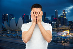 Man in white t-shirt covering his face with hands. People, travel, tourism, emotions and stress concept - man in white t-shirt covering his face with hands over Royalty Free Stock Photo