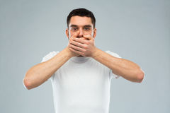 Man in white t-shirt covering his mouth with hands. Emotion, silence and people concept - man in white t-shirt covering his mouth with hands over gray background Stock Photography