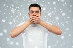 Man in white t-shirt covering his mouth with hands. Emotion, silence, winter, christmas and people concept - man in white t-shirt covering his mouth with hands Royalty Free Stock Images