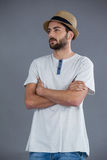 Man in white t-shirt and fedora hat. Against grey background royalty free stock photos