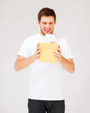 Man in white t-shirt with gift box Stock Photos