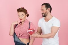 Man in white t-shirt gives beautiful brunette pin-up girl in denim a gift box with ribbon in the form of red heart. A stylish men in white shirt gives beautiful stock photography