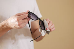 Man in white t shirt hand cleaning black sun glasses lens with i Royalty Free Stock Photo