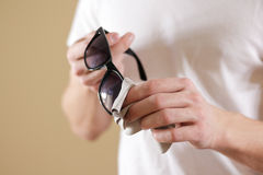 Man in white t shirt hand cleaning black sun glasses lens with i Stock Photos