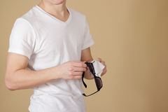 Man in white t shirt hand cleaning black sun glasses lens with i Stock Image