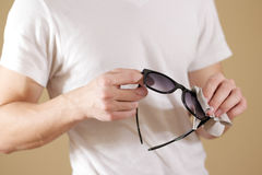 Man in white t shirt hand cleaning black sun glasses lens with i Stock Photography
