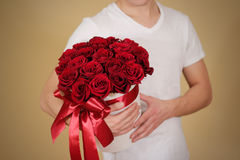 Man in white t shirt holding in hand rich gift bouquet of 21 red Royalty Free Stock Image