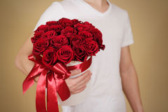 Man in white t shirt holding in hand rich gift bouquet of 21 red Royalty Free Stock Photo