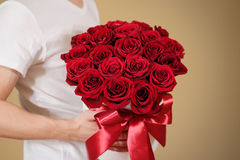 Man in white t shirt holding in hand rich gift bouquet of 21 red Stock Photos